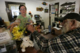 Bobbie Sterling, CQ, left, a manager at the Cutthroat Cafe, places flowers that were brought by a...