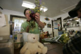 Bobbie Sterling, CQ, a manager at the Cutthroat Cafe, places flowers that were brought by a...