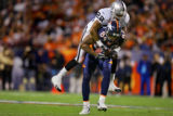 The Denver Broncos' Javon Walker (#84, WR) carries the Oakland Raiders'  Duane Starks (#22, CB) on...