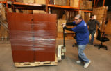 L to R: Eloy Gallegos (cq), and Jamal Billings (cq) unload Enron furniture at Office Liquidators...