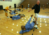 Denver Nuggets head coach George Karl, right, passes high-fives around as the Nuggets kicked off...