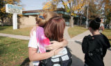 An Englewood H.S. student is hugged by a fellow student outside of Englewood H.S. after school...