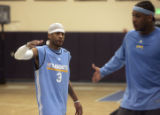 Allen Iverson (LEFT) offers a hand slap to Carmelo Anthony (right) at Nuggets practice Tuesday...