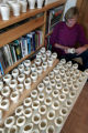 Annette Roberts Gray (cq) a potter, looks at some of the finished  memorial vases she makes in her...