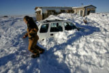 Shelby Wait (CQ), 9, walks over 10 foot snow drifts and the families buried cars to meet the...