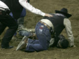 Members of the Justin Sports medicine rush to the aid of Myron Duarte, a bull rider from Auburn,...