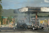 (FRISCO, COLO., AUGUST 4, 2004) Several burned vehicles smolder next to gas pumps while...
