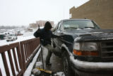 Justin Mestas, (cq), 19, works to clean off all the snow and ice possible on each incoming...