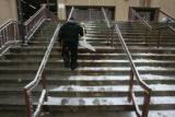 John Romero, (cq), climbs the steps near the end of a 6am-6pm shift shoveling. This day the snow...