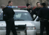 Denver cops survey the damage to a police car at Grant and Colfax Sunday, January 7, 2007, after...