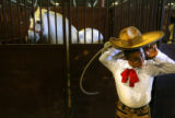 MJM407 Adolfo Farias (cq), 12, puts on his hat near horse stalls at the Denver Coliseum prior to...
