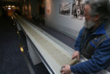 Jim Canary, (cq), Curator, unrolls the manuscript into the display case. Jack Kerouac's  On The...