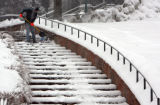 Scott McClintock (cq),21, shovels snow at the State Capitol complex as another blast of winter...