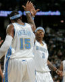 New Denver Nugget teammates Carmelo Anthony, left, and Allen Iverson, right, high five during the...