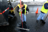 Mike Mestas, cq,  with Denver Public Works tamps down asphalt as he and Jesus Apodaca, cq, (Lt-rt)...