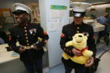 Sgt. Darylrion May, left and smiling, stands with Lance Corporal Michael Harris, holding a stuffed...
