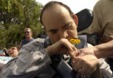 (DENVER, Colo., August 5 2004)  James Castro gets to observe a flower up close as Magda Ward and...
