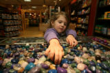 Avery Roche, (cq), 2-1/2, digs for the pinkish purplish stones while her mom watches in the gift...