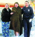 Cindy Trujillo (cq),center, is led away by a family friend (left) and a paramedic (right) from the...
