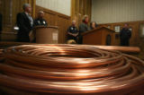 A coil of flexible copper tubing lays on a table during a press conference at the State Capitol...