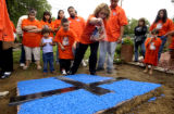 Denver, Colo.-July 23,2004-Barbara Lopez, widow of Eladio Lopez, sprinkles salt  on a cross placed...