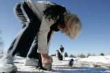Barbara Ruley  (cq) from Denver,tries to push a golf tee into the ground as she hits a bucket of...