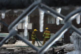 (DLM7628) -  Two firefighters can be seen through a frozen chain-link fence as they work to...