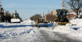 An unidentified man runs across the street as tractors work to remove snow from the Main St. in...