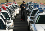 MJM193  A police officer walks through a line of police cruisers before the funeral for Aurora...