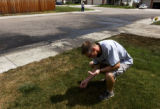(Fort Collins, Colo., July 25, 2004) Dylan Thomas, of Fort Collins, cleans glass and debris out of...