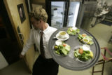 Server Jay Timp, CQ, caries house salads to customers at Bambino's at 1135 Bannok  in Denver,...