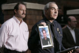 Aurora police Chief Daniel Oates holds a picture of slain officer Agent Michael Thomas at press...
