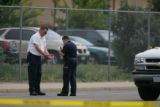 A Federal Bureau of Prisons officer, left, has his hands photographed on the scene where a plain...
