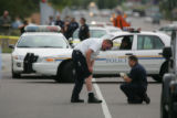 A Federal Bureau of Prisons officer, left, has his knees inspected  on the scene where a plain...