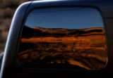 Aspens in full color in the San Juan Mountains are reflected in a jeep window Monday evening...