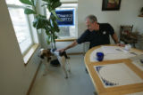 Bob Beauprez pets Petey (their sons dog) while sitting at his kitchen table in Arvada, Colo. on...