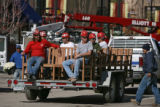 Workers sit on benches that are being delivered and will be set up by fountain area on Main Street...
