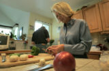 Claudia Beauprez cuts up some garlic for a pasta dish while Bob washes some vegetable to add to...