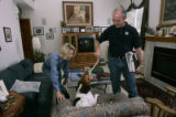 Bob Beauprez plays with Petey (their son's dog) along with Claudia in their living room in Arvada,...