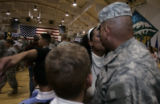 Sgt Samuel McCreary (cq)  is kissed by his wife Melody and greeted by his children Cheyanne,6 ,...