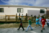 Third grade students at Second Creek Elementary School in Commerce City walk from their classroom,...