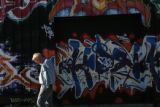 MJM584 David Steele (cq) walks in front of a building covered in graffiti that formerly held the...