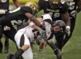 Texas Tech reciever Grant Walker gets tackled by University of Colorado Buffaloes defenders...
