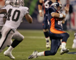 Denver Broncos quarterback Jake Plummer scrambles for a 11 yard pick up in the first quarter of...