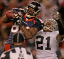 Denver Broncos wide reciever Javon Walker, left, grabs a 54-yard-pass being defended by Oakland...