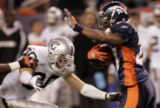 Denver Broncos kick returner Darrent Williams, right, avoids Oakland Raiders defender Stuart...
