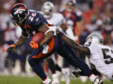 (RMN509) - Denver Broncos Tatum Bell drags  Oakland Raiders Kirk Morrison, #53, on a 16-yard pass...