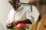 (DENVER, Colo., Aug. 10, 2004) Mitch Morrissey, ties a knot in a balloon, at his headquarters,...