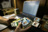Jose Mellado, CQ, 36, organizes a 56 card lot of 1964 Philadelphia football cards as he prepares...