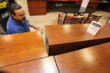 Mike Clever(cq) works on some Enron furniture recently unloaded at Office Liquidators in Lakewood...